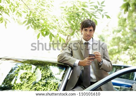 Attractive businessman leaning on a car's top while using a smart phone in a leafy street, smiling. - stock photo