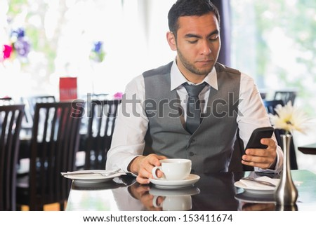 Attractive businessman sitting in restaurant and using his phone - stock photo
