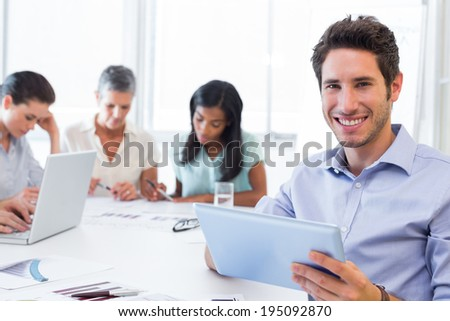 Attractive businessman smiling at the camera while using a tablet device in the office with coworkers behind - stock photo