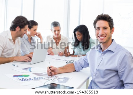 Attractive businessman smiling at the camera whilst working with coworkers