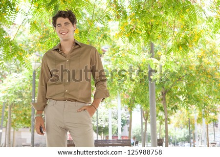 Attractive businessman standing in a city park under green trees in blossom, holding his smart phone in his hand, smiling. - stock photo