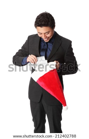 Attractive businessman standing wearing a suit and tie, holding a christmas hat full of money. Christmas bonus. White background.