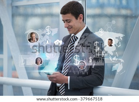 Attractive businessman using his smartphone with virtual icons and interface in office building - stock photo