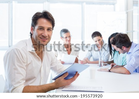 Attractive businessman using tablet device at work while smiling at the camera - stock photo