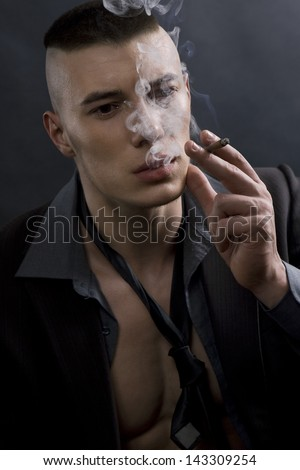 attractive businessman with a cigarette (man in a suit with a cigarette on a black background)