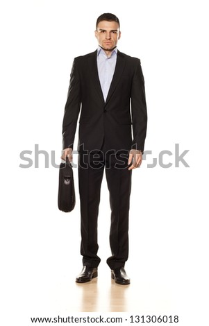 attractive businessman with a laptop bag posing on a white background - stock photo