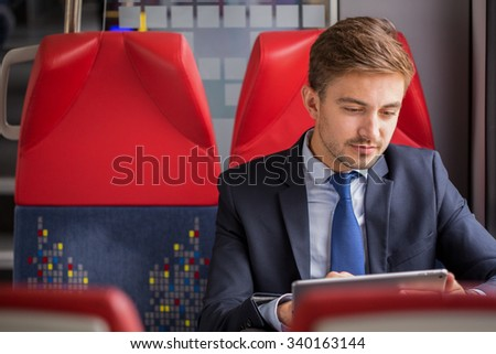 Attractive businessman with tablet working on a train - stock photo