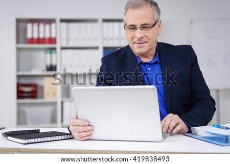 Attractive businessman working at his desk in the office on a laptop computer reading information on the screen with a serious expression