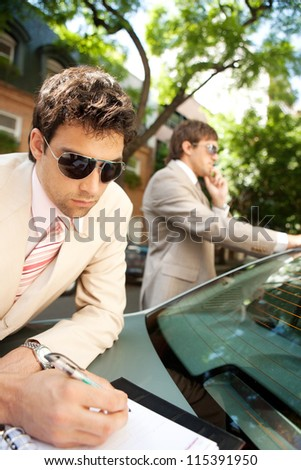 Attractive businessmen working together outdoors while leaning on a luxury car in a tree lined street. - stock photo