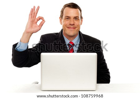 Attractive businessperson showing okay gesture to camera while working on laptop - stock photo