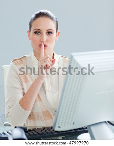 Attractive businesswoman at a computer asking for silence in the office