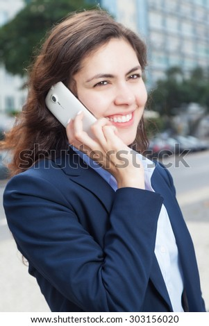 Attractive businesswoman at phone in the city - stock photo