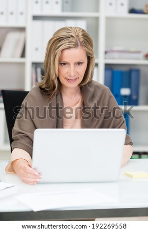 Attractive businesswoman at work at her desk in the office concentrating as she reads information on the screen of her laptop computer - stock photo