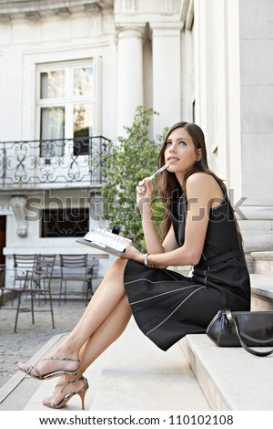 Attractive businesswoman being thoughtful while sitting in a colonial building's stairs, outdoors. - stock photo