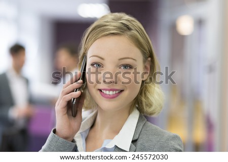 Attractive businesswoman calling with cell phone in modern office. looking camera - stock photo