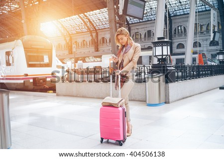 attractive businesswoman checks the e-mail while waiting for the train. attractive young blonde woman using smart-phone while standing on the railway station platform - stock photo
