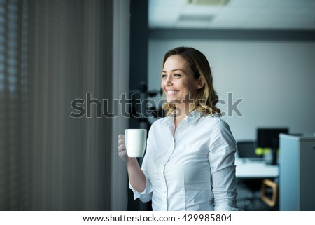 Attractive businesswoman drinking coffee next to the window in an office. - stock photo