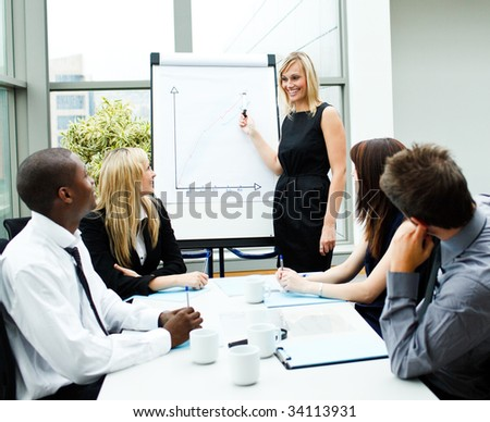 Attractive businesswoman giving a presentation to her team - stock photo