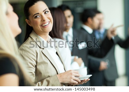 attractive businesswoman having fun conversation with colleague during break - stock photo