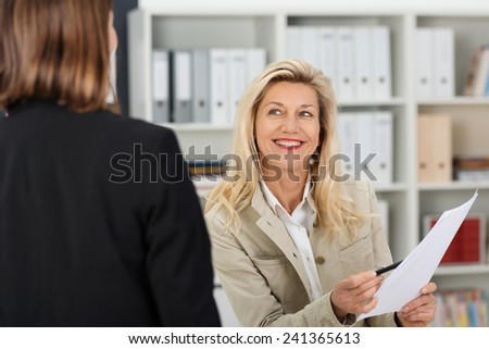 Attractive businesswoman holding a paper document chatting to a colleague looking at her with a beaming smile