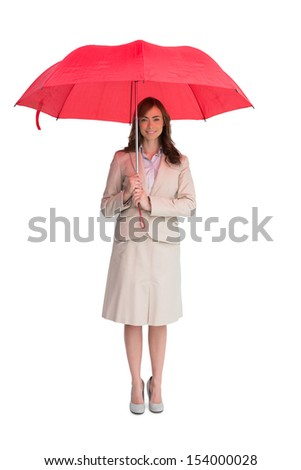 Attractive businesswoman holding red umbrella against white background - stock photo