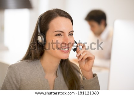 Attractive Businesswoman in office on the phone, headset - stock photo