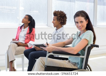 Attractive businesswoman in wheelchair smiling in the workplace in the office