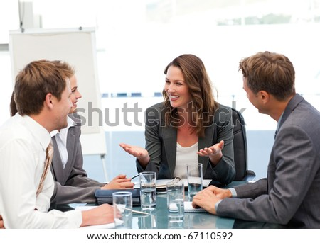 Attractive businesswoman laughing with her team - stock photo