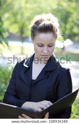 Attractive Businesswoman Looking Over Portfolio - stock photo
