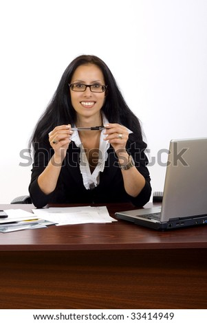 attractive businesswoman on her desk holding a pen
