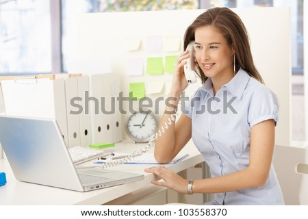 Attractive businesswoman on landline phone call, sitting at desk, looking at screen.