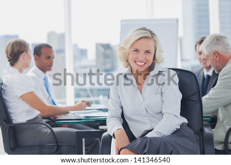 Attractive businesswoman posing in the boardroom with colleagues discussing behind - stock photo