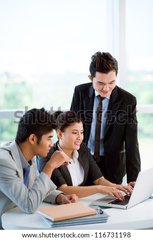Attractive businesswoman presenting new ambitious project to her male colleagues - stock photo