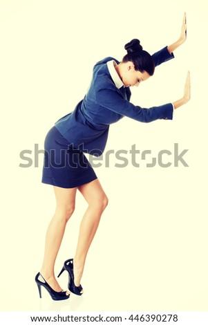 Attractive businesswoman pushing something - stock photo
