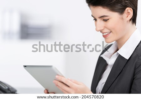 Attractive businesswoman reading a tablet computer smiling as she reads the information on the screen, profile view with copyspace - stock photo