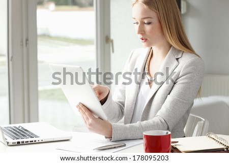 Attractive businesswoman sitting at desk and typing on tablet in office.
