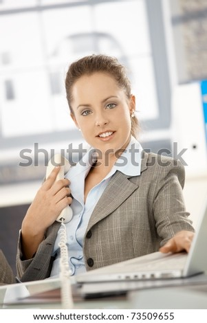 Attractive businesswoman sitting at desk in office, holding phone, having laptop, smiling. - stock photo