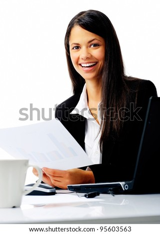 attractive businesswoman sitting at her desk, reading stats and graphs on paperwork while enjoying a cup of coffee and smiling isolated on white