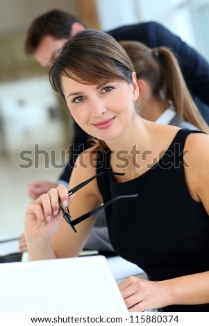 Attractive businesswoman sitting in office with workteam - stock photo