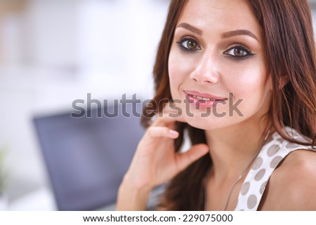 Attractive businesswoman sitting  in the office, isolated - stock photo