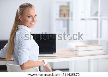 Attractive businesswoman sitting on a desk with laptop in the o - stock photo