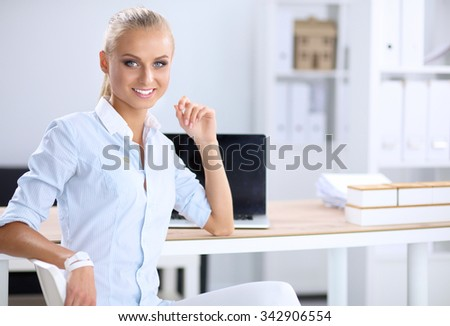 Attractive businesswoman sitting on a desk with laptop in the office - stock photo