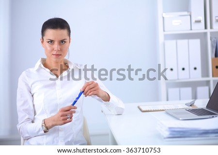 Attractive businesswoman sitting on a desk with laptop in the office