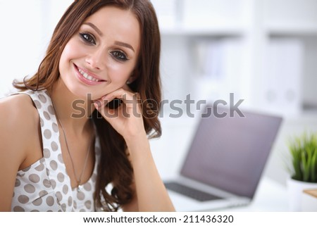 Attractive businesswoman sitting  on desk in the office - stock photo