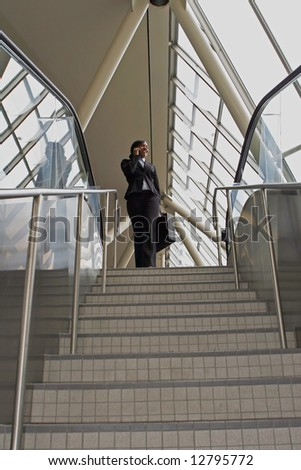 Attractive businesswoman smiling and talking on her phone as she stands at the top of the stairs. Vertically framed, wide angle shot.