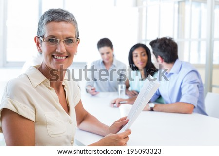 Attractive businesswoman smiling at the camera during a business meeting