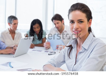 Attractive businesswoman smiling at the camera during a business meeting - stock photo