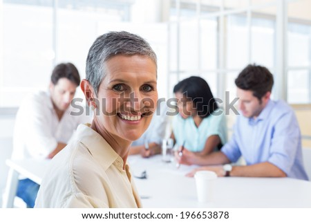 Attractive businesswoman smiling at the camera in the workplace with other coworkers