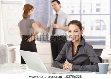 Attractive businesswoman smiling happily in office, sitting at desk, having laptop, colleagues chatting in background. - stock photo