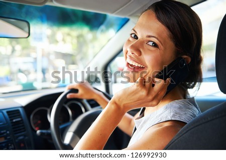 attractive businesswoman smiling while talking on the phone and driving to work, happy carefree business - stock photo